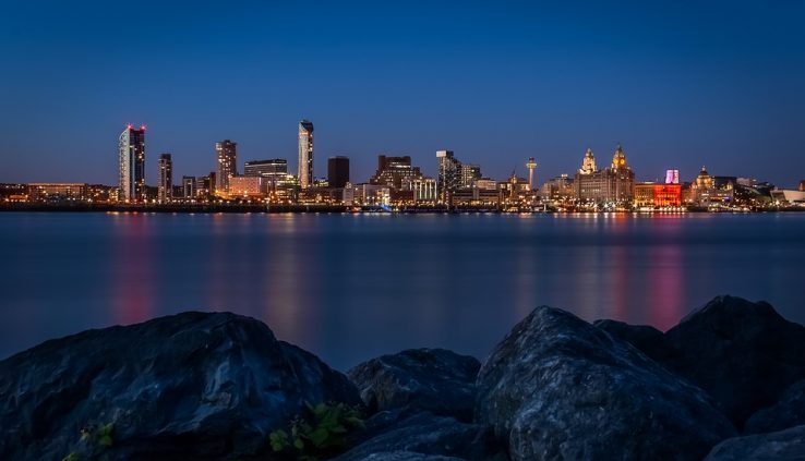 picture taking on rocks, with water visible and a city beyond the water, a place I would ponder changing