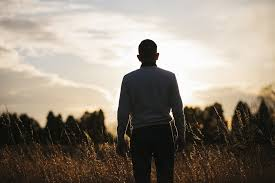 Man staring at the sky while pondering. The light is hitting him but we see his back and he is facing away.