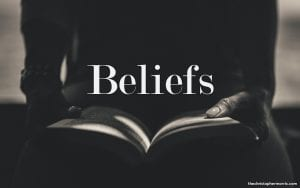 a man with an open book on his lap, the word beliefs spelled in the center of the iamge
