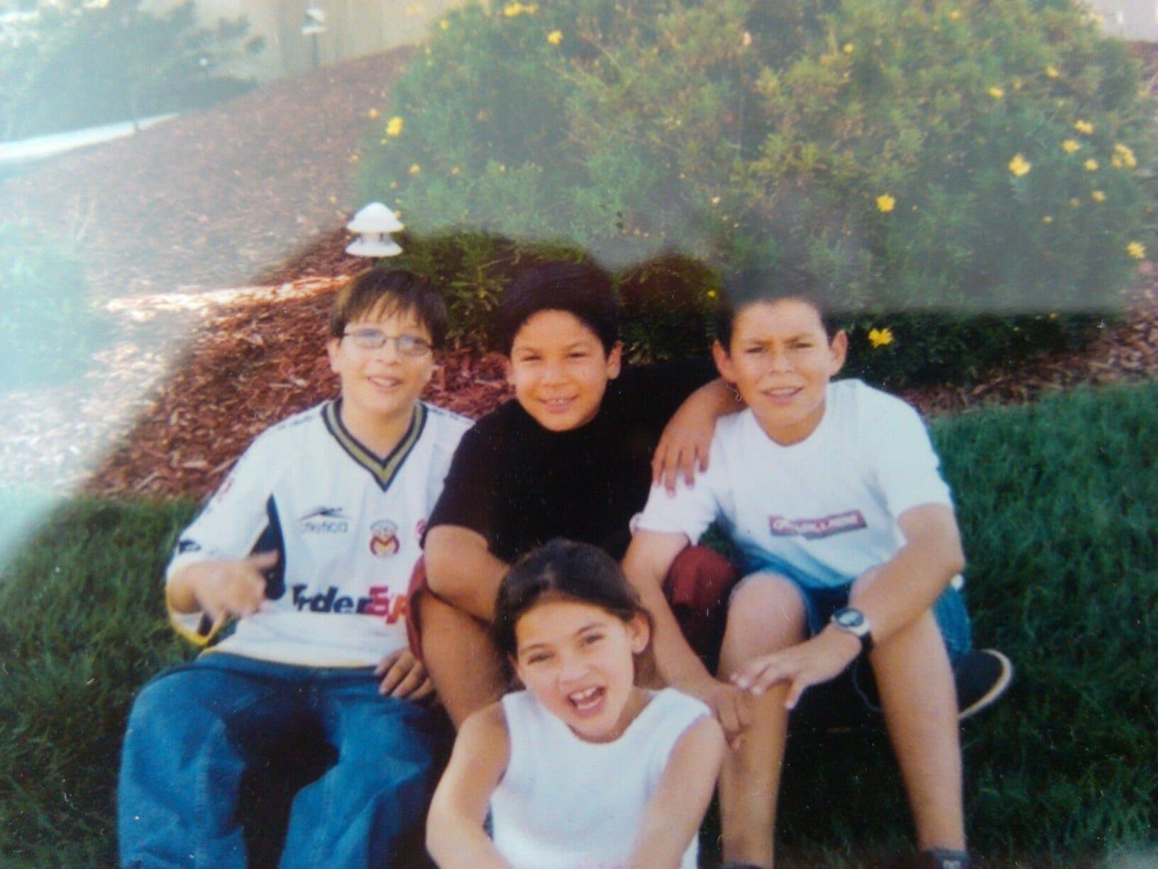 Jose Moreno, Javy Moreno, Anthony Moreno, and Samantha Moreno sitting on the grass