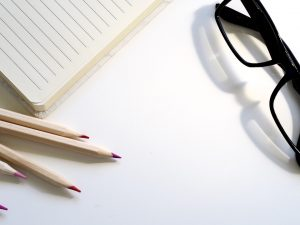 a picture of 3 pencils on top of white paper with black glasses halfway showing at the top right corner