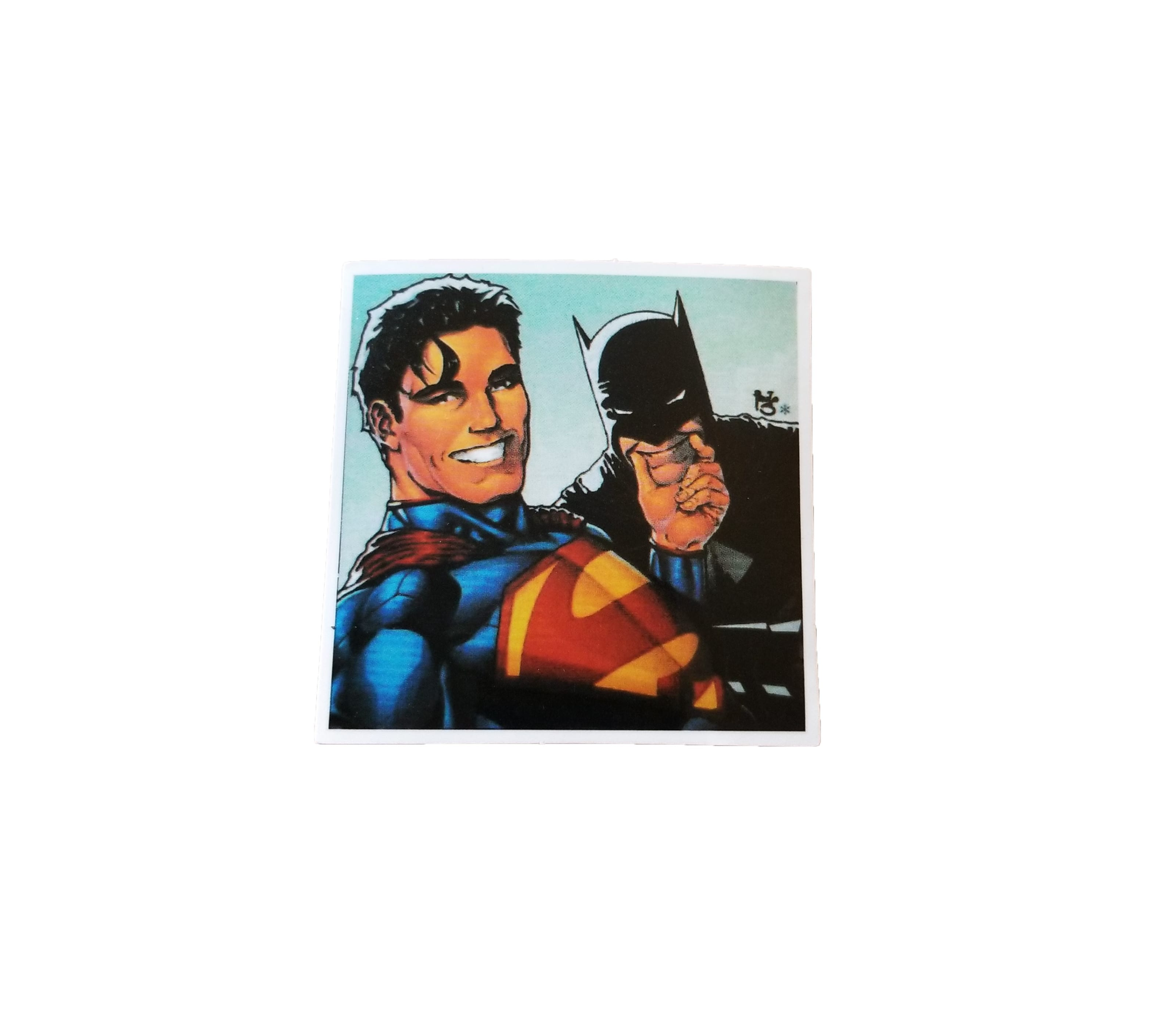 A sticker of Superman smiling while holding Batman by the Chin